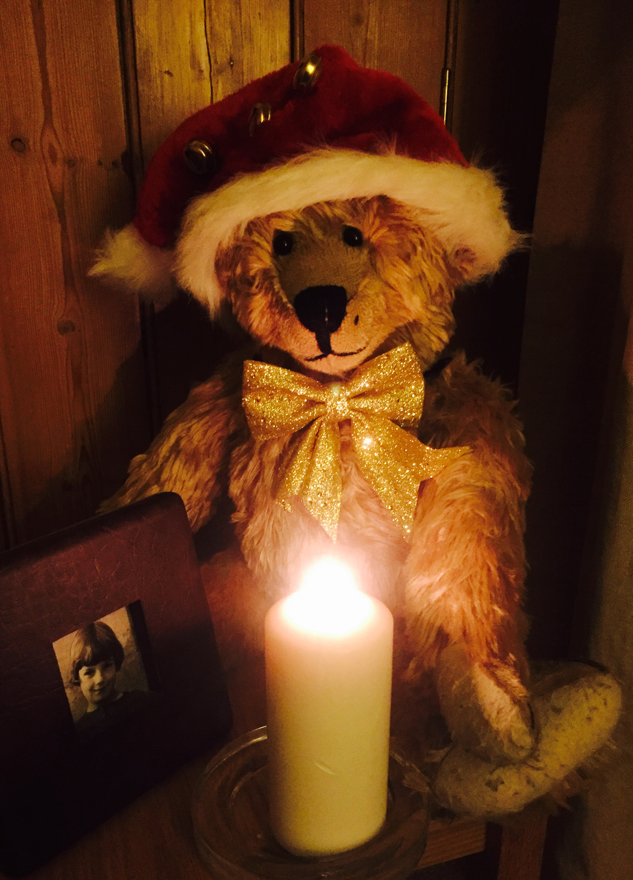 Bertie wearing a Christmas Santa hat sat looking at a lit candle.